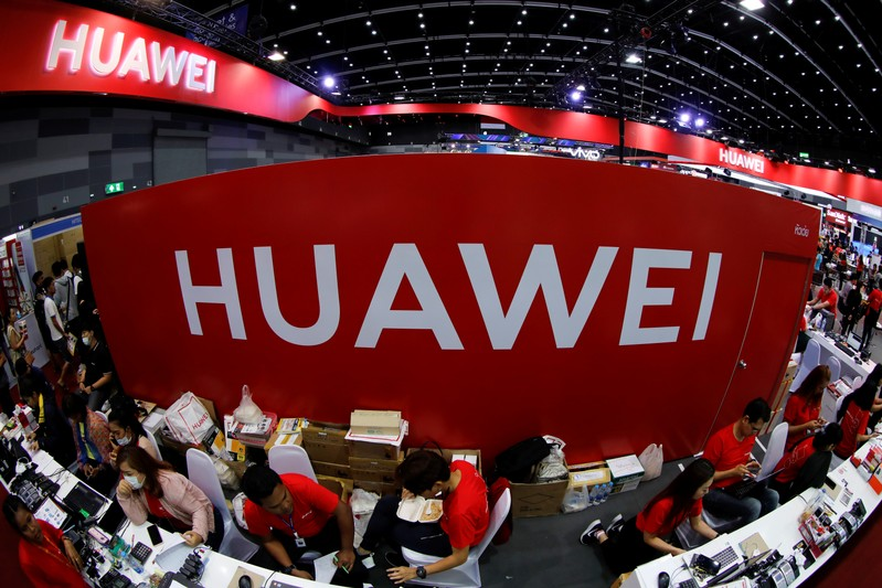 FILE PHOTO: Workers sit at the Huawei stand at the Mobile Expo in Bangkok