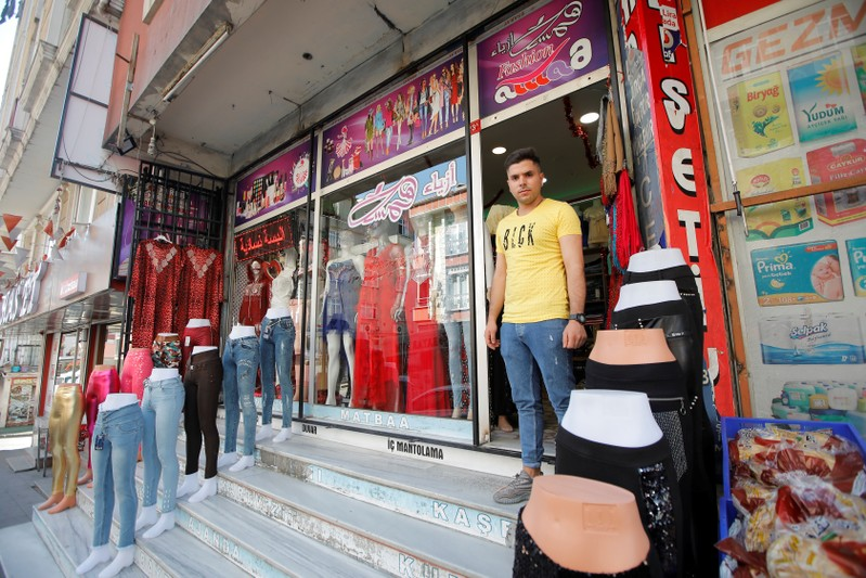 Syrian shopkeeper Mustafa poses in front of his clothes shop in Istanbul's Kucukcekmece district