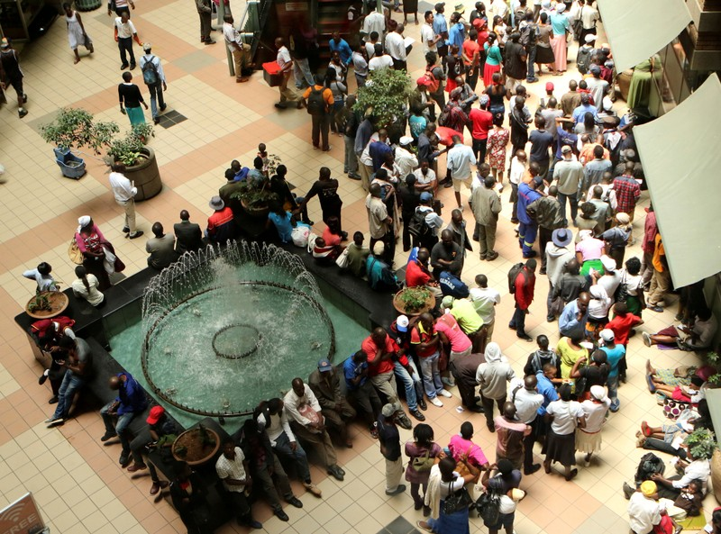 FILE PHOTO: People queue to withdraw money from a bank in Harare
