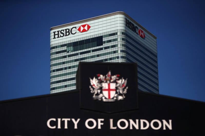 HSBC's building in Canary Wharf is seen behind a City of London sign outside Billingsgate Market in London