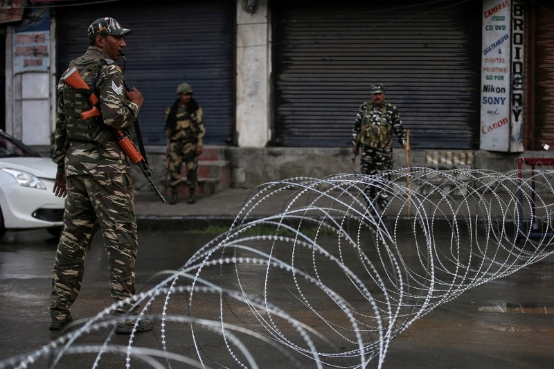 FILE PHOTO: Indian security forces personnel stand guard next to concertina wire laid across a road during restrictions after the government scrapped special status for Kashmir, in Srinagar