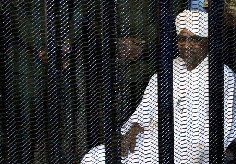 FILE PHOTO: Sudan's former president Omar Hassan al-Bashir sits guarded inside a cage at the courthouse where he is facing corruption charges, in Khartoum