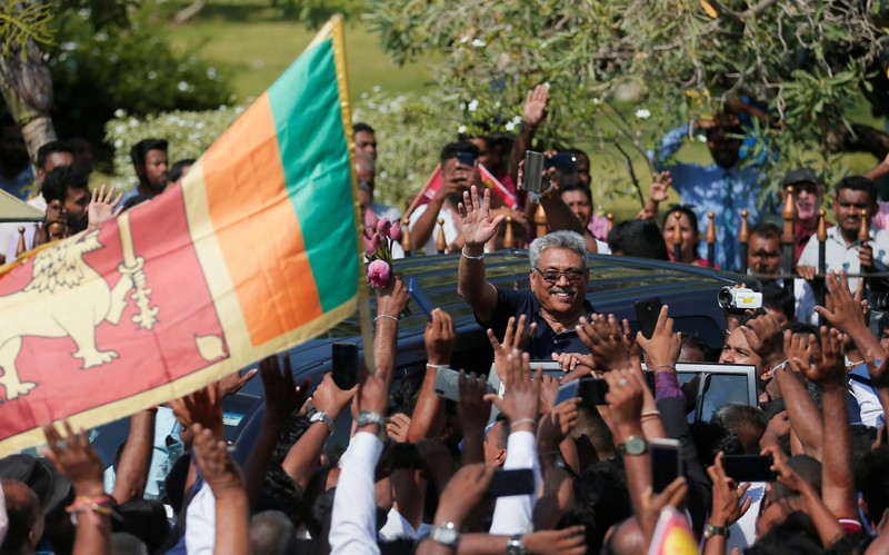 FILE PHOTO: Sri Lanka's former defense secretary Rajapaksa gestures at his supporters after he returned from United States of America in Katunayake