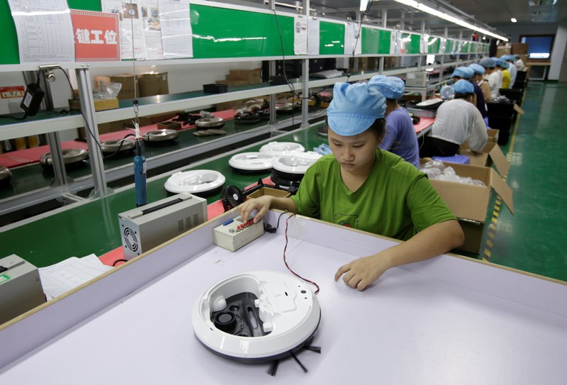 FILE PHOTO: An employee works on the production line of a robot vacuum cleaner at a factory of Matsutek in Shenzhen