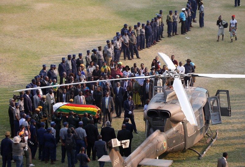 The casket carrying the body of former Zimbabwean President Robert Mugabe is carried to the military chopper after lying in state at the Rufaro stadium