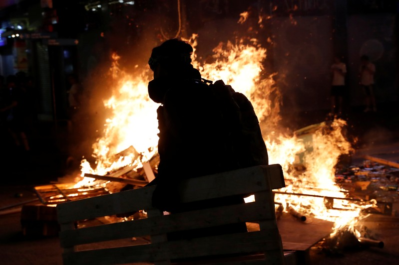 An anti-extradition bill protester walks near a burning barricade during a protest at Mong Kok in Hong Kong