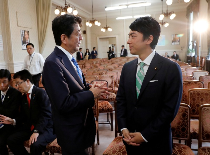 FILE PHOTO: Japan's Prime Minister Shinzo Abe talks with his party's lawmaker Shinjiro Koizumi at the party lawmakers' meeting after the dissolution of the lower house was announced at the Parliament in Tokyo