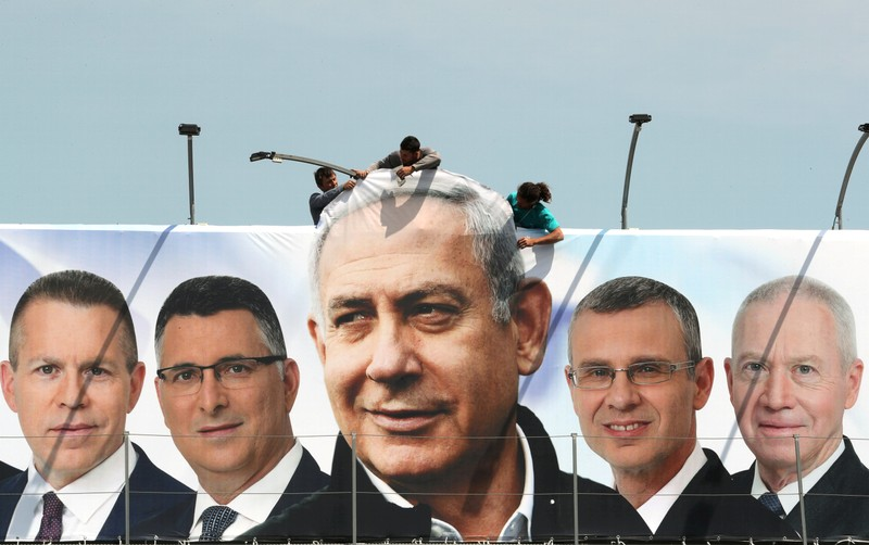 FILE PHOTO: Labourers work on hanging up a Likud election campaign banner depicting Israeli Prime Minister Benjamin Netanyahu with his party candidates, in Jerusalem