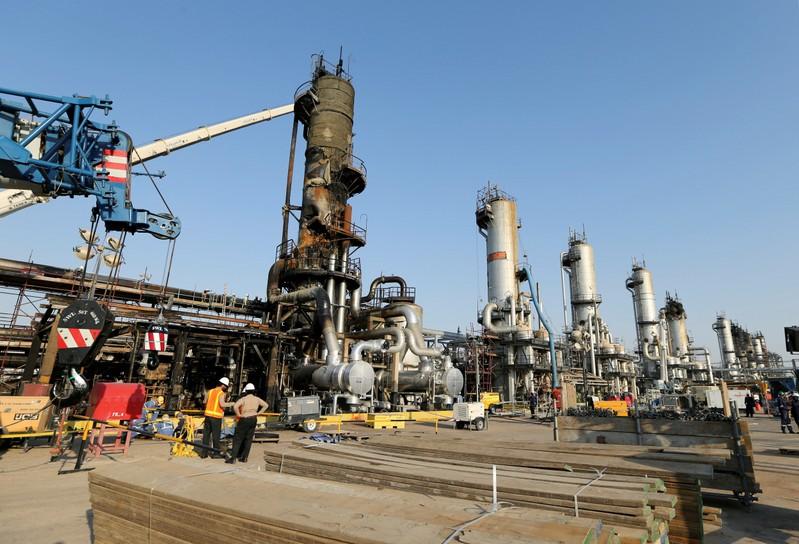 FILE PHOTO: Workers are seen at the damaged site of Saudi Aramco oil facility in Abqaiq