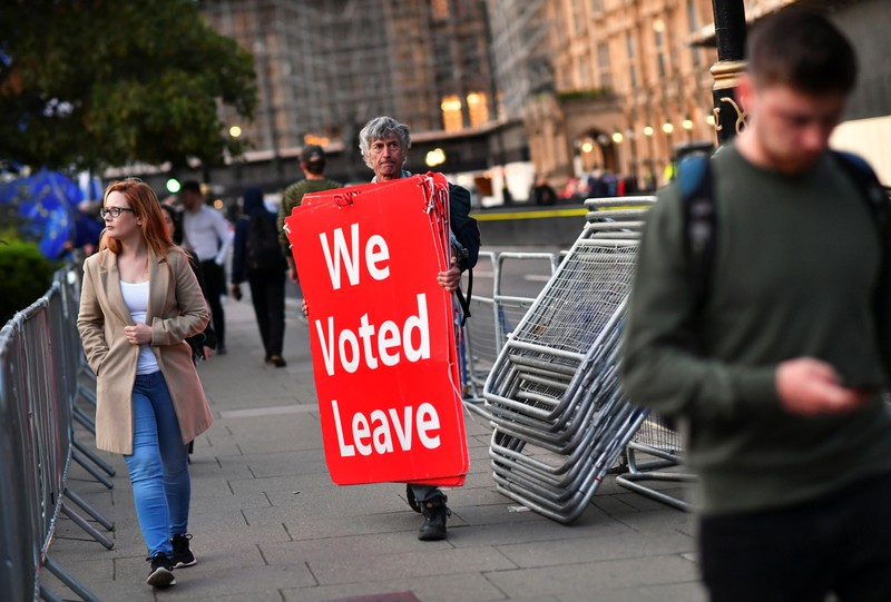 Pro-Brexit protester carries signs outside the Houses of Parliament in London