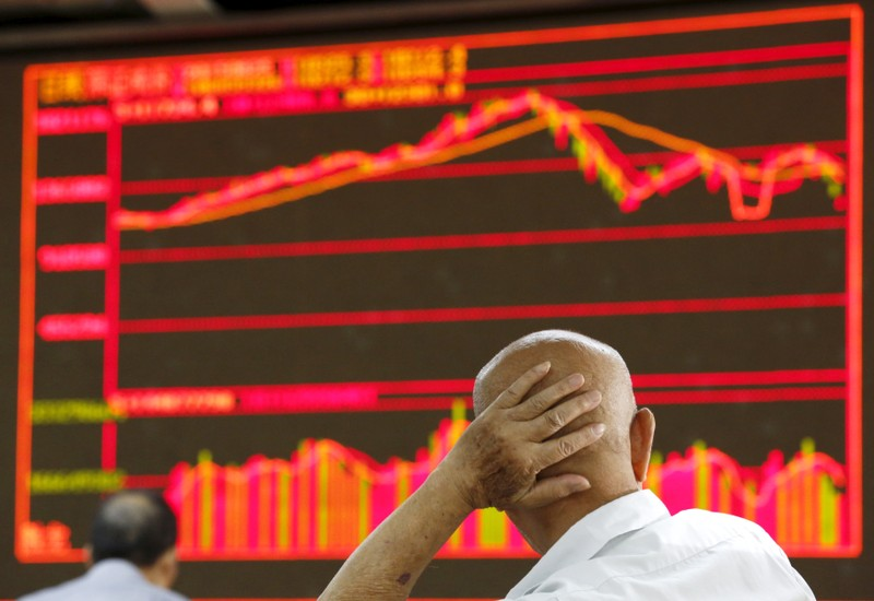 An investor looks at an electronic board showing stock information at a brokerage house in Beijing