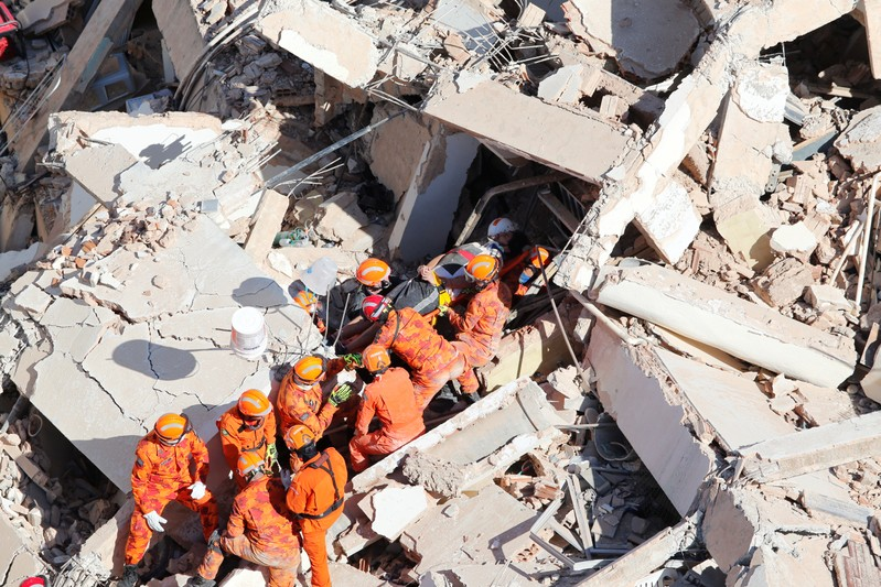 Rescue workers carry a victim after a seven-story residential building collapsed in Fortaleza