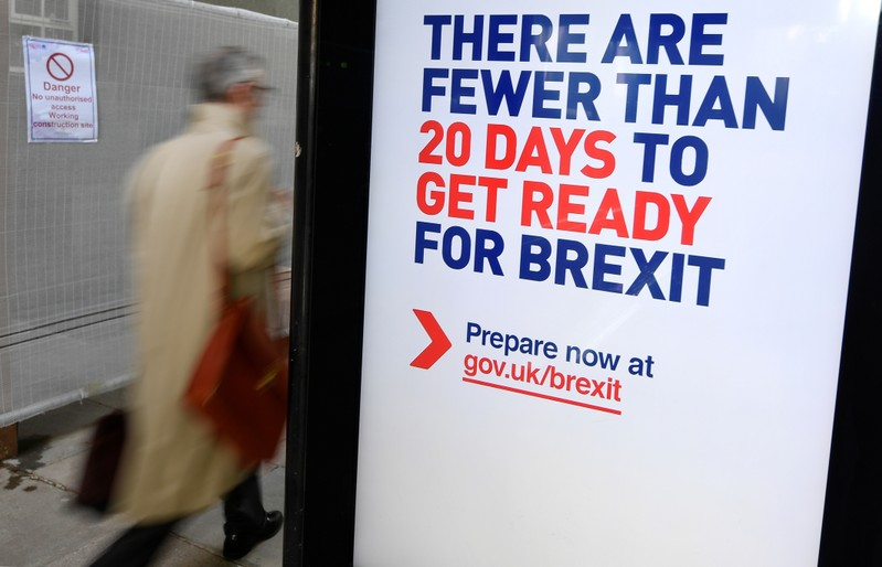 A man walks past an UK government Brexit information campaign poster at a bus stop in central London