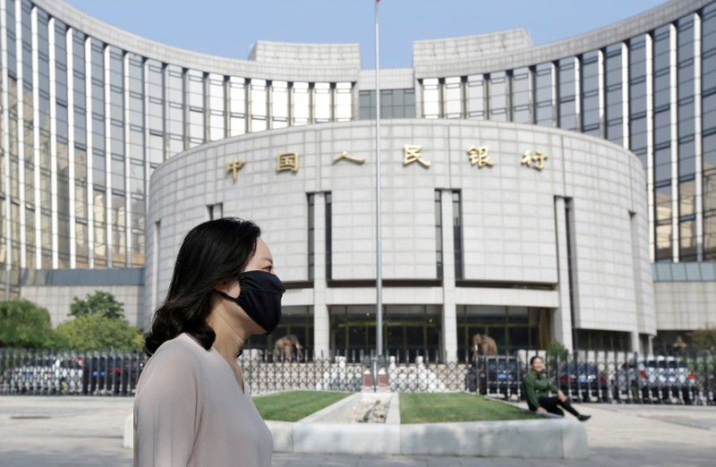 FILE PHOTO: A woman walks past the headquarters of the PBOC, the central bank, in Beijing