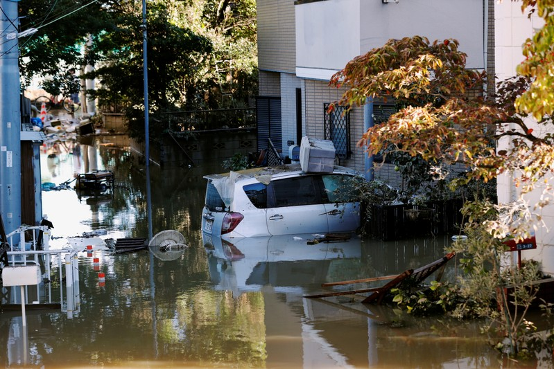 A car is seen partially submerged in a flooded residential area due to Typhoon Hagibis, near the Tama River in Kawasaki, Japan