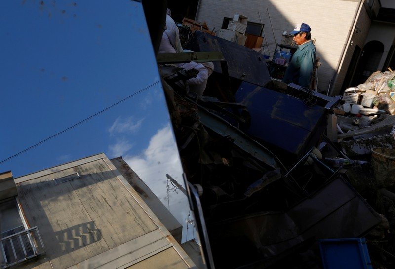 A man is seen near damaged belongings, in the aftermath of Typhoon Hagibis, in Yanagawamachi district, Date City