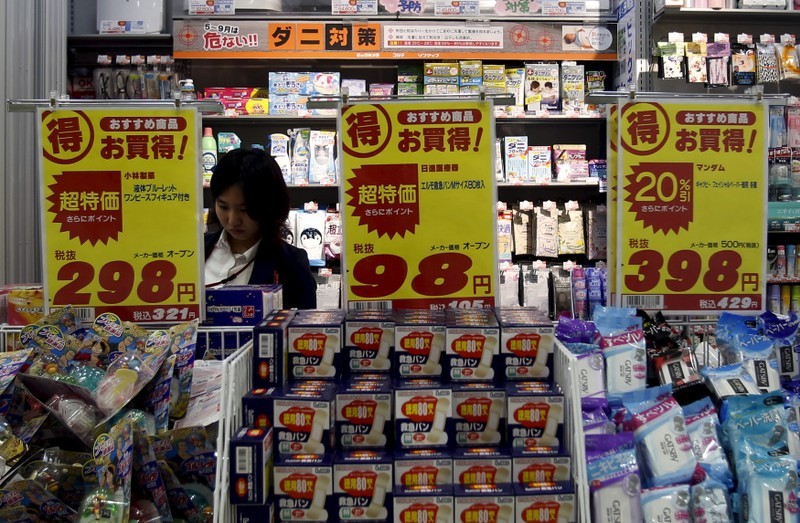 A shopper is seen between price boards at a drug store in Tokyo