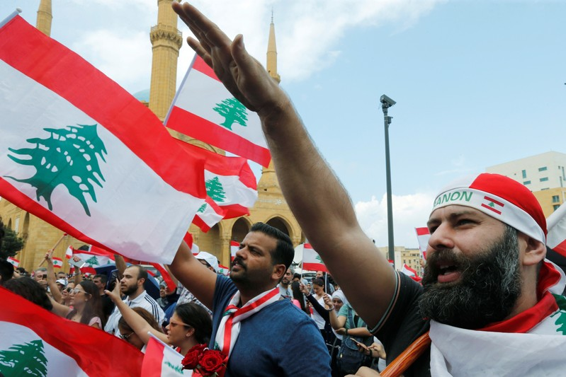 Demonstrators carry national flags and gesture during an anti-government protest in downtown Beirut