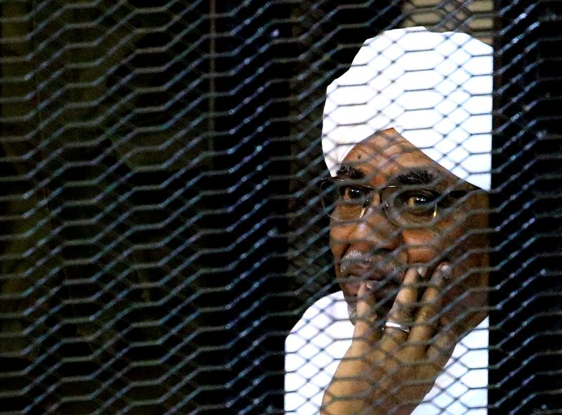 FILE PHOTO: Sudan's former president Omar Hassan al-Bashir sits inside a cage at the courthouse where he is facing corruption charges, in Khartoum