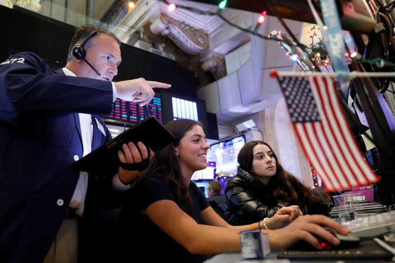 Trader Jonathan Corpina works with children during a traditional bring-your-kids-to-work day on the floor at the NYSE in New York