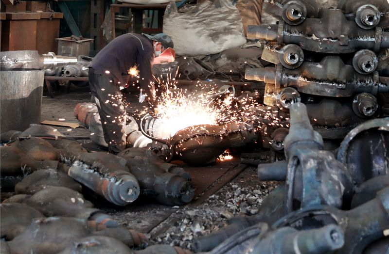 Worker welds automobile parts at a workshop manufacturing automobile accessories in Huaibei, Anhui