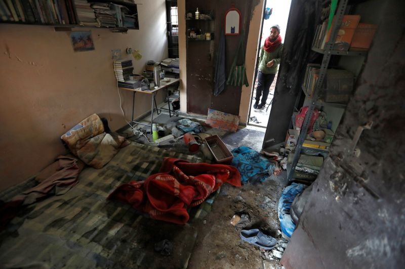 A student of Jawaharlal Nehru University looks at a damaged hostel room after it was attacked by a mob on Sunday, in New Delhi