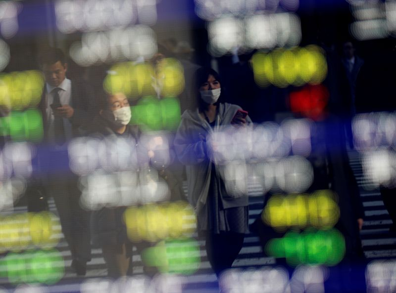 Pedestrians wearing facial masks are reflected on an electric board showing stock prices outside a brokerage at a business district in Tokyo