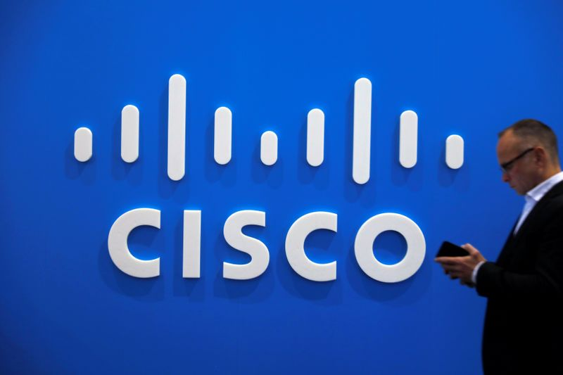 A visitor uses a mobile phone in front of the Cisco booth at the Mobile World Congress in Barcelona