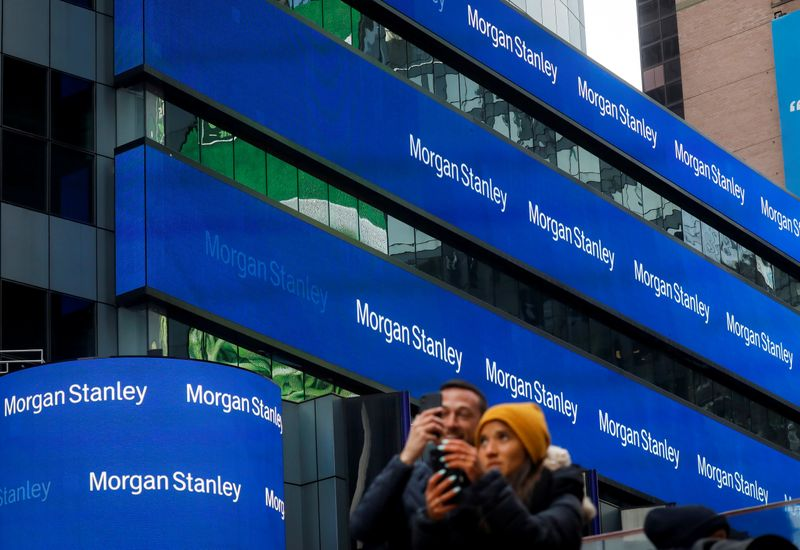 People take photos by the Morgan Stanley building in Times Square in New York