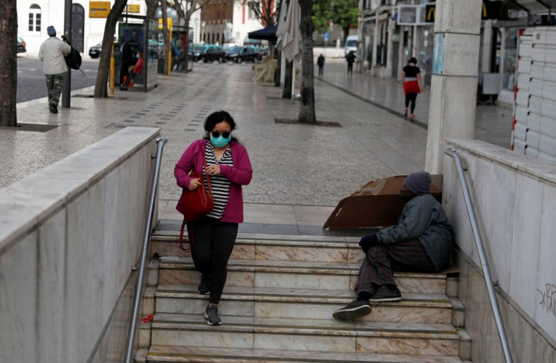 FILE PHOTO: A woman wearing a protective mask as a preventive measure against coronavirus disease (COVID-19) enters the subway at Rossio Square in downtown Lisbon