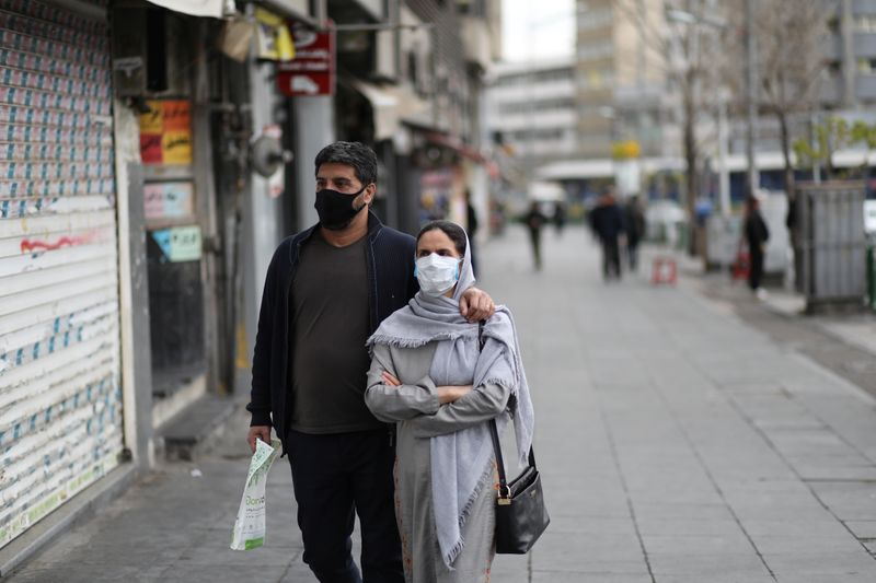 Couple wear protective face masks, amid fear of coronavirus disease (COVID-19), as they walk at Enghelab square, in Tehran