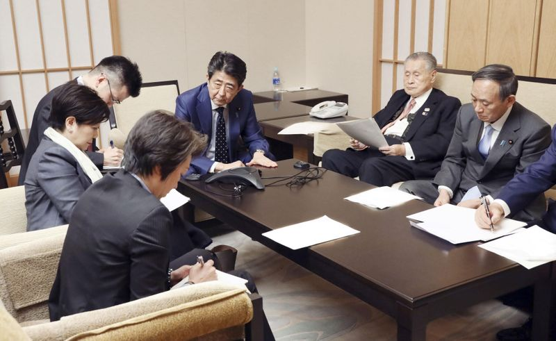 Japan's Prime Minister Shinzo Abe, President of the Tokyo 2020 Organizing Committee Yoshiro Mori, Tokyo Governor Yuriko Koike, and ministers attend a telephone conference with IOC President Bach in Tokyo