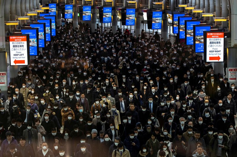 FILE PHOTO: Crowds wearing protective masks, following an outbreak of the coronavirus, are seen at the Shinagawa station in Tokyo