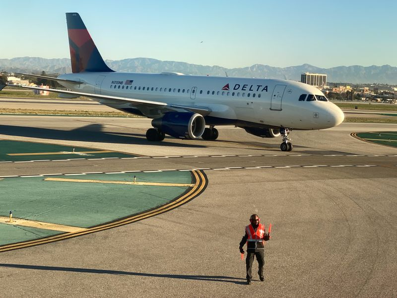 An airport worker guides a Delta Air Lines Airus A319 plane on the tarmac at LAX in Los Angeles