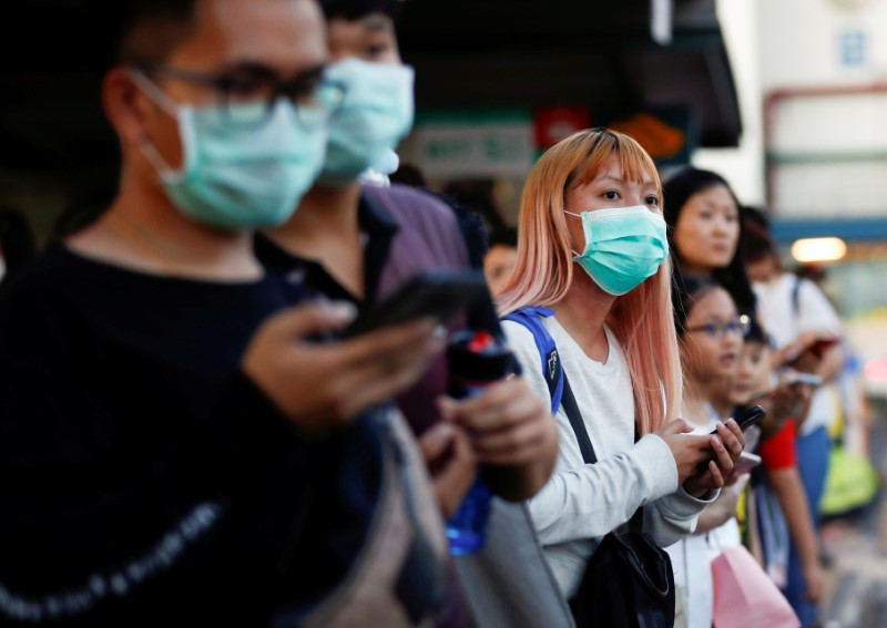 FILE PHOTO: Commuters wait for a transport to leave the Woodlands Causeway across to Singapore from Johor, hours before Malaysia imposes a lockdown on travel due to the coronavirus outbreak