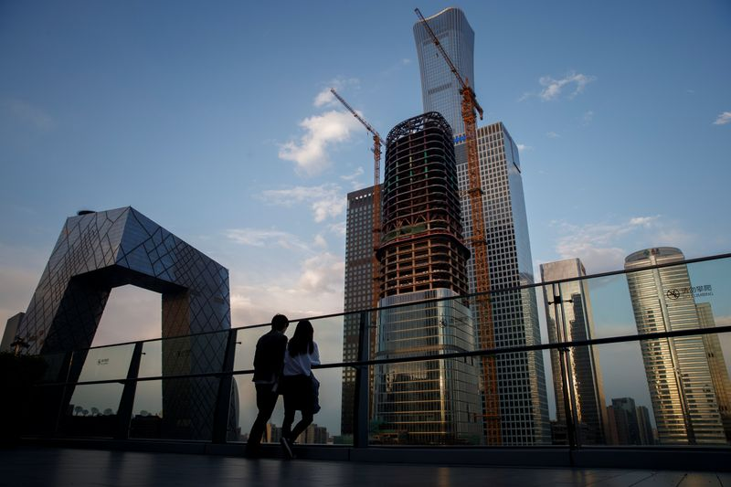 People look at the skyline of the Central Business District in Beijing