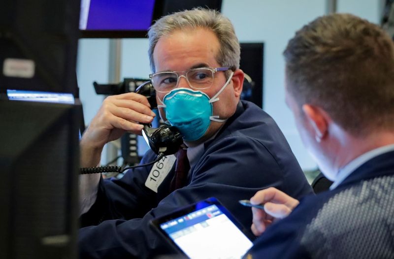 FILE PHOTO: A trader wears a face mask on the floor of the NYSE in New York