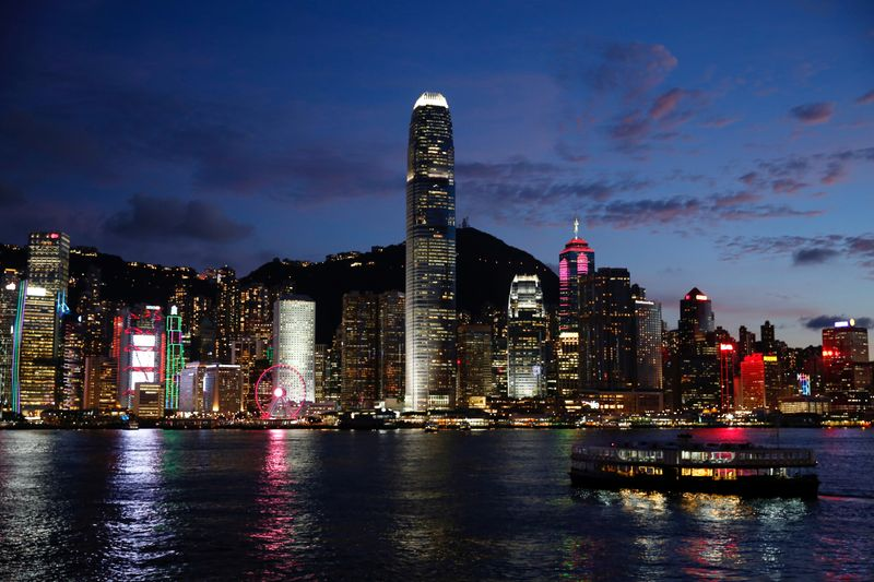 A Star Ferry boat crosses Victoria Harbour in front of a skyline of buildings during sunset, as a meeting on national security legislation takes place in Hong Kong