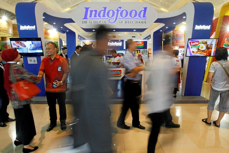FILE PHOTO: Visitors walk past the booth of Indonesian food giant Pt. Indofood Sukses Makmur at a trade exhibition in Jakarta,