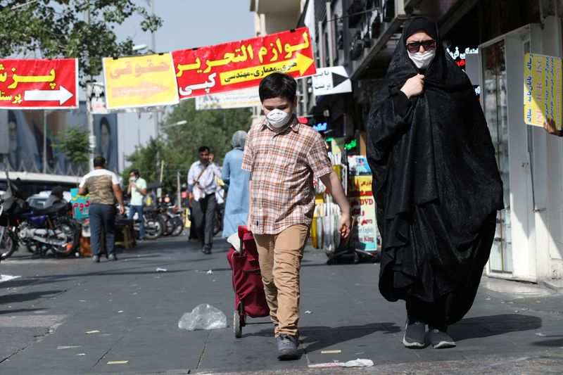 FILE PHOTO: An Iranian woman and her son wearing a protective face mask walks the street, following the outbreak of the coronavirus disease (COVID-19), in Tehran