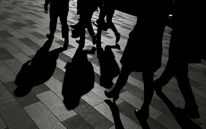 FILE PHOTO: Workers cast shadows as they stroll among the office towers Sydney's Barangaroo business district in Australia's largest city