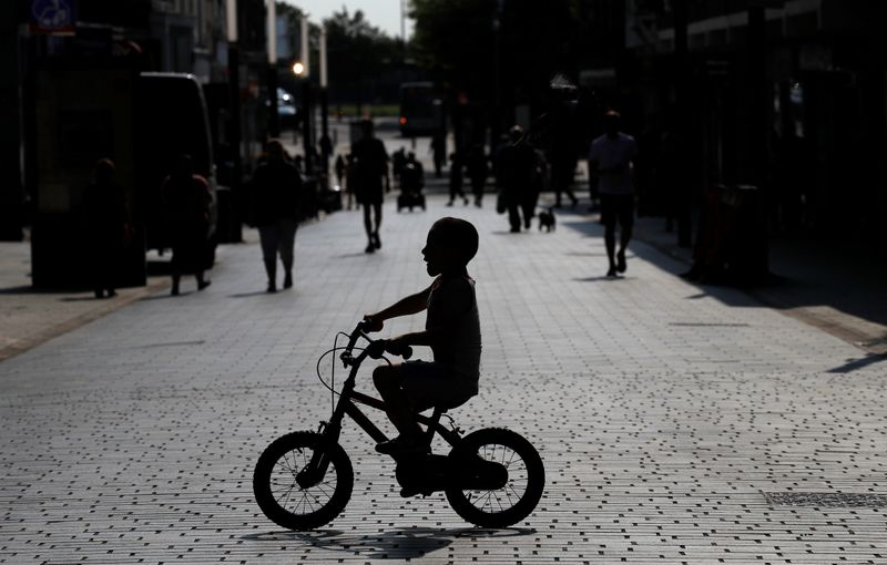 FILE PHOTO: A child cycles his bike across a quiet shopping street following the outbreak of the coronavirus disease (COVID-19) in St Helens
