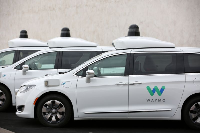 FILE PHOTO: Three of the fleet of 600 Waymo Chrysler Pacifica Hybrid self-driving vehicles are parked and diaplayed during a demonstration in Chandler, Arizona