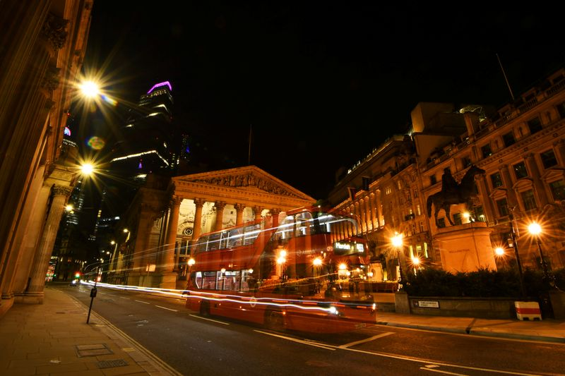 An empty bus is driven through the quiet streets outside the Bank of England in the early hours in London