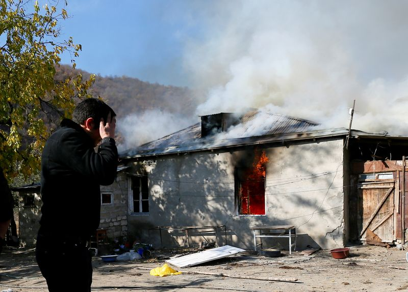 A man reacts as he stands near a house set on fire by departing Ethnic Armenians in the village of Cherektar, in the region of Nagorno-Karabakh