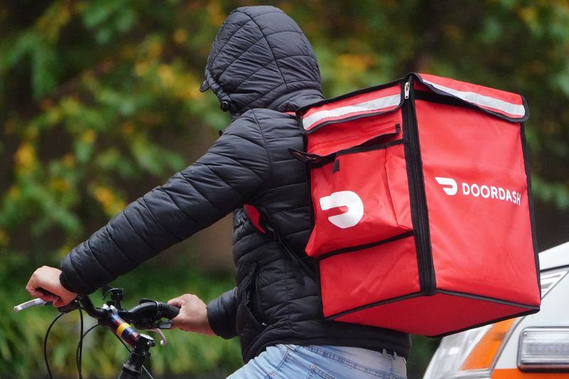 A delivery person for Doordash rides his bike in the rain during the coronavirus disease (COVID-19) pandemic in the Manhattan borough of New York City
