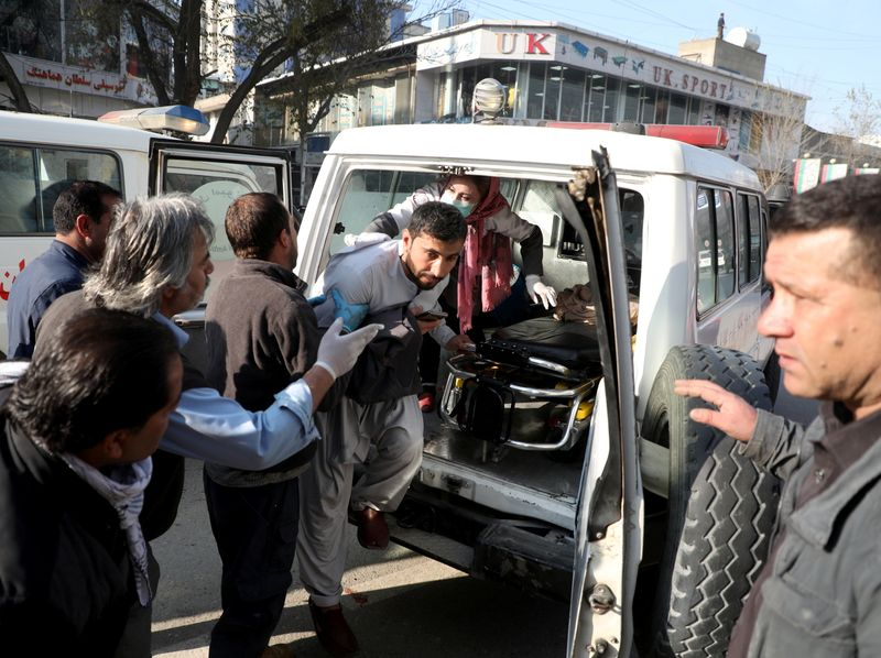 An injured man is carried to a hospital after rockets hit residential areas in Kabul