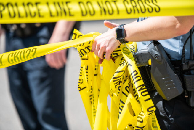 MINNEAPOLIS, MN - JUNE 16: A Minneapolis Police officer rolls up caution tape at a crime scene on June 16, 2020 in Minneapolis, Minnesota. The Minneapolis Police Department has been under close scrutiny following the death of George Floyd who died in police custody on May 25, 2020, after former officer Derek Chauvin kneeled on his neck for nearly nine minutes while detaining him. (Photo by Brandon Bell/Getty Images)