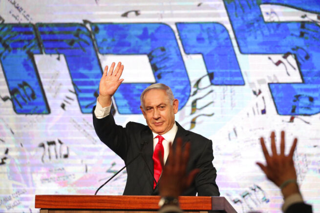 FILE - In this Wednesday, March. 24, 2021 file photo, Israeli Prime Minister Benjamin Netanyahu waves to his supporters after the first exit poll results for the Israeli parliamentary elections at his Likud party's headquarters in Jerusalem. After a hard-fought election, an Arab Islamist, Mansour Abbas, leader of the United Arab List, also known by the Hebrew name Ra'am, could choose Israel's next prime minister. Tuesday's elections have left a razor-thin margin between a right-wing coalition led by Netanyahu and a diverse array of parties bent on ousting him. Each side needs the support of Ra'am. (AP Photo/Ariel Schalit, `file)