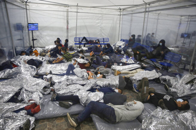 Young children rest inside a pod at the U.S. Customs and Border Protection facility, the main detention center for unaccompanied children in the Rio Grande Valley, in Donna, Texas, Tuesday, March 30, 2021. The children are housed by the hundreds in eight pods that are about 3,200 square feet in size. Many of the pods had more than 500 children in them. The Biden administration for the first time allowed journalists inside its main detention facility at the border for migrant children, revealing a severely overcrowded tent structure where more than 4,000 kids and families were crammed into pods and the youngest kept in a large play pen with mats on the floor for sleeping. (AP Photo/Dario Lopez-Mills, Pool)